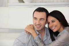 Paare, die auf dem Sofa umarmen Stockbilder