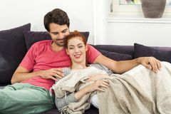 Paare, die auf dem Sofa am Wohnzimmer stillstehen Stockbilder