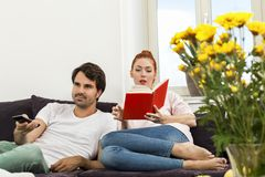 Paare, die auf dem Sofa am Wohnzimmer stillstehen Stockfotos