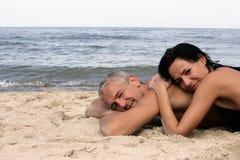 Paare, die auf dem Strand sich entspannen Stockbilder
