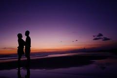 Paare, die auf dem Strand stehen Stockbild