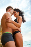 Paare, die auf dem Strand umarmen Lizenzfreies Stockbild