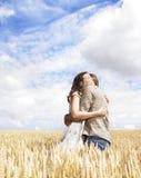 Paare, die auf dem Weizengebiet umarmen Lizenzfreie Stockbilder