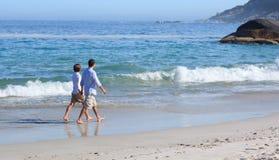 Paare, die auf den Strand gehen stockbild