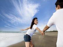 Paare, die auf den Strand laufen Stockbild