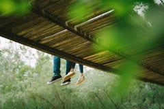 Paare, die auf der Brücke sitzen Stockbilder
