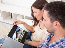 Paare, die auf der Couch betrachtet Bild von Real Estate sitzen Lizenzfreie Stockfotografie