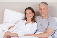 Paare, die auf einem Bett liegen Stockbilder