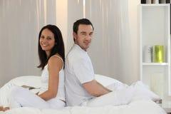 Paare, die auf einem Bett sitzen Stockfotos