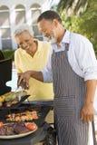 Paare, die auf einem Grill kochen Lizenzfreie Stockfotos