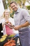 Paare, die auf einem Grill kochen Stockfotos