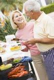 Paare, die auf einem Grill kochen Lizenzfreies Stockfoto