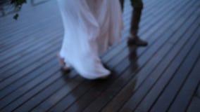 Paare, die auf einem nassen Bretterboden laufen stock footage