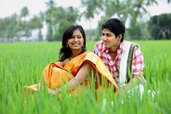 Paare, die auf einem Paddygebiet sitzen lizenzfreie stockfotografie