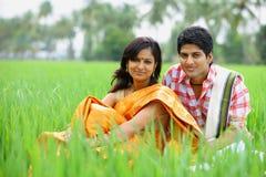Paare, die auf einem Paddygebiet sitzen Lizenzfreie Stockfotos