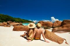 Paare, die auf einem Strand bei Seychellen sitzen Lizenzfreie Stockfotografie