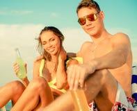Paare, die auf einem Strand sich entspannen Lizenzfreie Stockfotografie