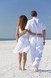 Paare, die auf einen leeren Strand gehen Lizenzfreie Stockfotos
