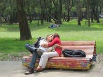 Paare, die auf einer bunten Parkbank küssen Lizenzfreie Stockfotos