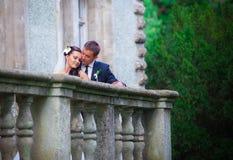 Paare, die auf Gebäudebalkon küssen Stockbild