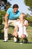 Paare, die auf Golfplatz Golf spielen lizenzfreie stockbilder