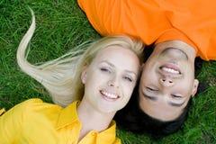 Paare, die auf Gras liegen Stockbild
