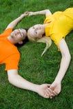 Paare, die auf Gras liegen lizenzfreies stockbild