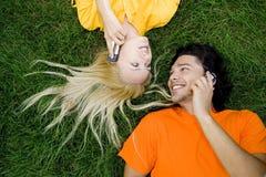 Paare, die auf Gras liegen Lizenzfreies Stockfoto