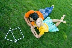 Paare, die auf Gras mit vorbildlichem Haus liegen Stockbild
