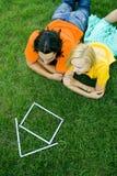 Paare, die auf Gras mit vorbildlichem Haus liegen Stockfotos