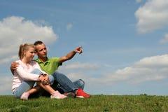Paare, die auf Gras sitzen Stockbild