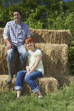 Paare, die auf Hay Bales sitzen Lizenzfreies Stockfoto