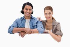 Paare, die auf leerer Wand sich lehnen Lizenzfreie Stockbilder
