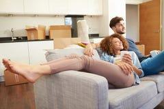 Paare, die auf neuem Haus Sofa With Hot Drink Ins sich entspannen Stockfoto