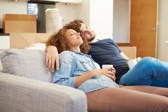 Paare, die auf neuem Haus Sofa With Hot Drink Ins sich entspannen Stockfotografie