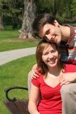 Paare, die auf Parkbank sitzen Stockbild