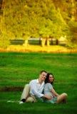 Paare, die auf Parkrasen sitzen Stockbilder