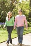 Paare, die auf Pfadholding-Handdem lächeln gehen stockfotografie