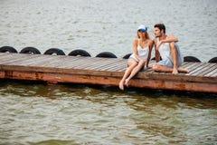 Paare, die auf Pier sitzen und sprechen Lizenzfreie Stockfotos