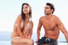 Paare, die auf Poolrand sitzen Lizenzfreie Stockbilder