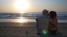 Paare, die auf sandigem Strand bei Sonnenaufgang küssen stock video footage