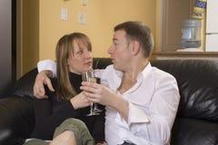 Paare, die auf schwarzer Couch sitzen Lizenzfreie Stockfotos