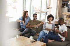 Paare, die auf Sofa With Friends At Home-Unterhaltung sitzen Stockfotografie