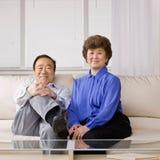 Paare, die auf Sofa im Wohnzimmer sich entspannen Stockfotos