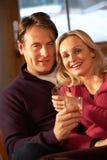 Paare, die auf Sofa mit Gläsern Whisky sitzen Stockfoto