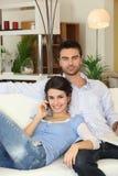 Paare, die auf Sofa sich entspannen Lizenzfreies Stockbild
