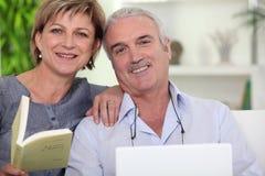 Paare, die auf Sofa sich entspannen Stockbilder