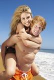 Paare, die auf Strand huckepack tragen Stockfotos