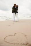 Paare, die auf Strand küssen Stockfoto