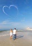 Paare, die auf Strand schlendern Lizenzfreies Stockfoto